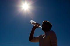 Acque in bottiglia beventi dell'uomo sotto il sole Fotografie Stock