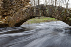 Acque di inondazione a flusso rapido con gli arché di pietra Fotografia Stock