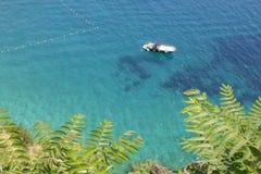 Acque tropicali vaghe con la barca di galleggiamento Fotografie Stock