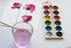 Acquerelli, strumenti artistici e pittura di bei fiori rosa su fondo bianco, posto di lavoro artistico Fotografie Stock Libere da Diritti