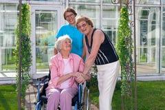 Acquirenti sorridenti di cura per il paziente anziano su sedia a rotelle Fotografia Stock