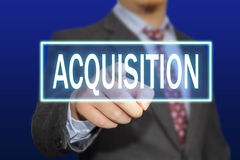 Acquisition Concept. Business concept image of a businessman clicking Acquisition button on virtual screen over blue background stock image