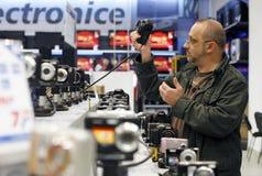 Acquistando per le macchine fotografiche digitali della foto in supermercato Immagine Stock Libera da Diritti
