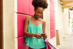 Acquisto afroamericano e invio di messaggi di testo della ragazza sul telefono immagini stock libere da diritti