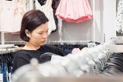 Acquisto asiatico della donna nel deposito dei vestiti di modo Fotografie Stock