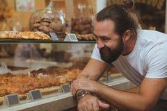 Acquisto bello barbuto dell'uomo al forno locale immagini stock libere da diritti