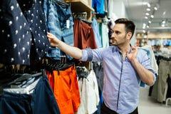 Acquisto bello dell'uomo per i vestiti fotografia stock libera da diritti