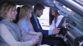 Acquisto dei veicoli della famiglia, giovani coppie con la ragazza sveglia del bambino che parla dell'automobile d'acquisto con l