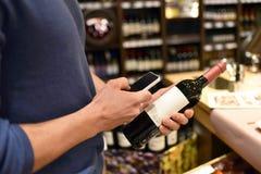 Acquisto del supermercato con lo smartphone - valuti il confronto e le informazioni fotografia stock libera da diritti