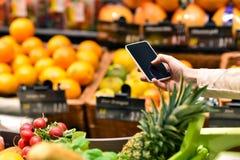 Acquisto del supermercato con lo smartphone - valuti il confronto e le informazioni fotografia stock