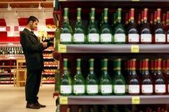 Acquisto del vino e dell'alcool al supermercato Fotografia Stock Libera da Diritti