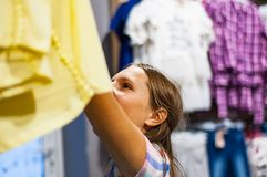 Acquisto dell'adolescente per i vestiti dentro il negozio di vestiti Fotografia Stock Libera da Diritti