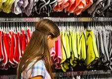 Acquisto dell'adolescente per i vestiti dentro il negozio di vestiti Immagine Stock
