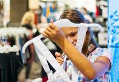 Acquisto dell'adolescente per i vestiti dentro il negozio di vestiti Fotografie Stock