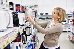 Acquisto della casalinga della donna per il bollitore elettrico immagini stock libere da diritti