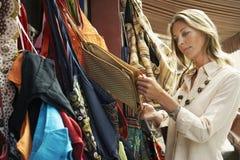 Acquisto della donna per le borse sulla stalla del mercato Fotografie Stock Libere da Diritti