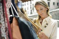 Acquisto della donna per le borse sulla stalla del mercato Fotografie Stock