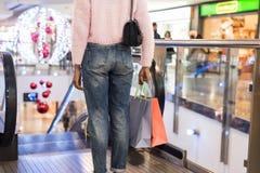 Acquisto della donna sullo scalator in un centro commerciale fotografia stock libera da diritti