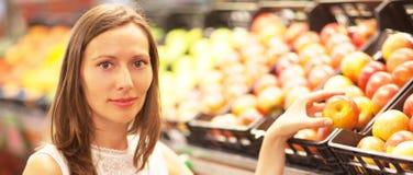 Acquisto della donna in un negozio della frutta fotografia stock