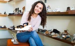 Acquisto della giovane donna al negozio di scarpe di modo Fotografia Stock