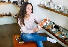 Acquisto della giovane donna al negozio di scarpe di modo Immagini Stock