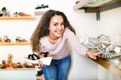 Acquisto della giovane donna al negozio di scarpe di modo Fotografia Stock Libera da Diritti