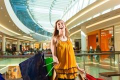 Acquisto della giovane donna nel viale con i sacchetti Fotografia Stock