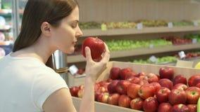 Acquisto della giovane donna nella drogheria per alimento sano Ragazza del vegano che sceglie le mele rosse fresche stock footage