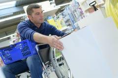 Acquisto della sedia a rotelle dell'en dell'uomo immagine stock libera da diritti