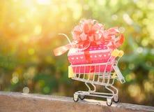 Acquisto di giorno di biglietti di S. Valentino e contenitore di regalo/scatola attuale rosa con l'arco rosso del nastro sul carr fotografia stock