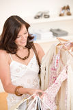 Acquisto di modo - la donna felice sceglie i vestiti di vendita immagini stock libere da diritti