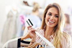 Acquisto felice della donna per i vestiti con la carta di credito Fotografia Stock