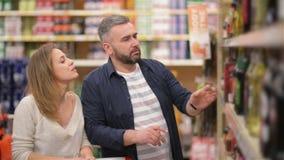 Acquisto felice delle coppie nel supermercato Giovane famiglia che sceglie vino dagli scaffali del supermercato video d archivio