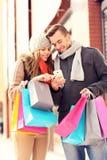 Acquisto felice delle coppie nella città con lo smartphone Immagine Stock