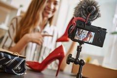 Acquisto in linea Blogger grazioso e giovane che mostra le sue scarpe rosse del tacco alto online ai suoi abbonati fotografie stock libere da diritti
