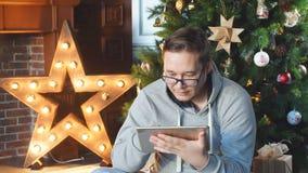 Acquisto in linea L'uomo sceglie i regali di Natale sul touchpad archivi video