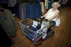 Acquisto maggiore della donna con un buggy Fotografia Stock