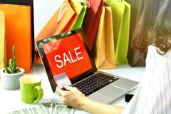 Acquisto online, carta di credito della tenuta della donna di Shopaholic, segno di promozione di vendita sul computer portatile Fotografia Stock