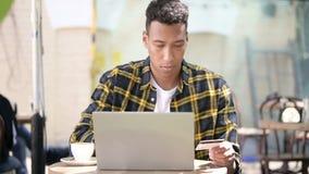 Acquisto online sul computer portatile dal giovane uomo africano, caffè all'aperto video d archivio