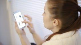 Acquisto online, una giovane donna che passa in rassegna le merci nel deposito online sullo schermo dello smartphone video d archivio