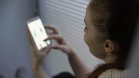 Acquisto online, una giovane donna che passa in rassegna le merci nel deposito online sullo schermo dello smartphone stock footage