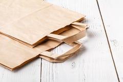 Acquisto Sacchi di carta vuoti con le maniglie, responsabilità sociale, concetto di cura di ecologia fotografia stock libera da diritti