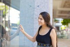 Acquisto teenager biraziale della finestra della ragazza, esaminante gla della parte anteriore del deposito Immagine Stock