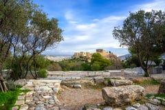 Acrópole com Partenon Vista através de um quadro de plantas verdes, de árvores e de mármores antigos, Atenas fotos de stock royalty free