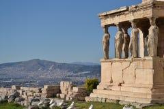 Acrópolis, Atenas, Karyatides con paisaje urbano y el cielo azul imagen de archivo libre de regalías