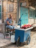 The seller of freshly squeezed juices sits and smokes nargila in anticipation of buyers on the market in the old city of Acre in I. Acre, Israel, November 03 Royalty Free Stock Photography
