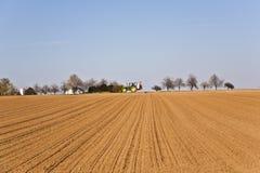 Acre recentemente ploughed com fileira das árvores Fotografia de Stock Royalty Free
