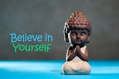 Acredite no senhor mesmo seguro incentivam o conceito da motivação com o bebê meditando ou rezando buddha foto de stock