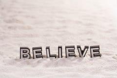 Acredite a palavra na areia branca imagem de stock royalty free