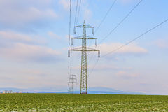 Acres with snow in winter with electricity tower in sunset Stock Image